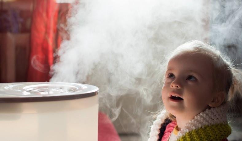 Image of infant girl next to humidifier releasing mist vapor