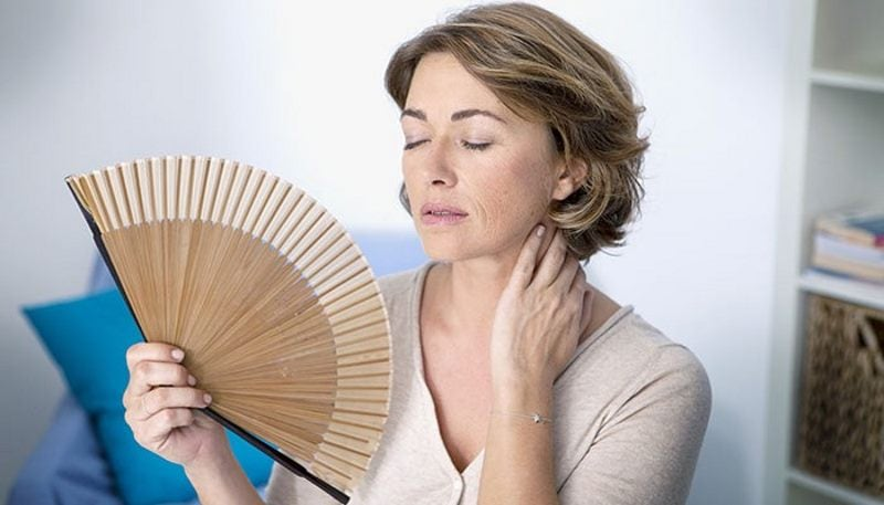 Image of a woman sweating and cooling with a fan due to high humidity