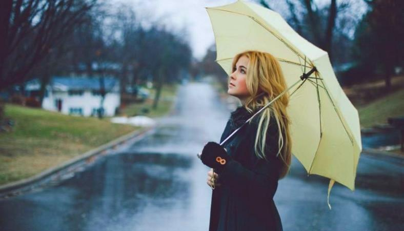 Image of a woman standing in rain with umbrella