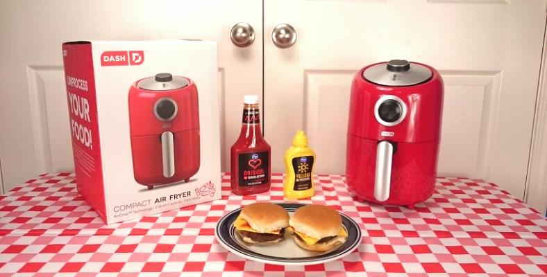 Display image of Dash air fryer with cooked hamburgers