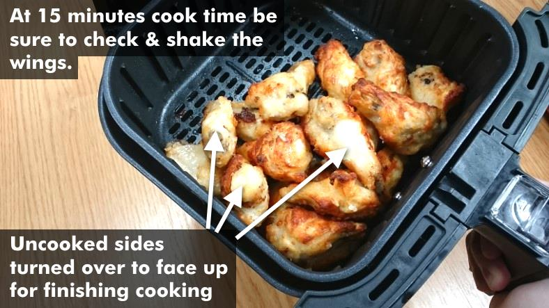Image with diagram showing example of partially cooked chicken wings in air fryer after shaking