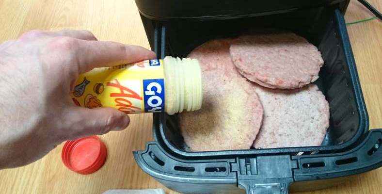 Image showing adding seasoning to frozen patties in air fryer before cooking