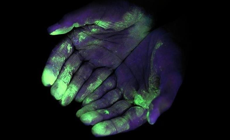 Image showing example of germs on hands in blacklight UV